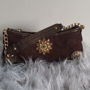 A new day handbag with a green pin on the front